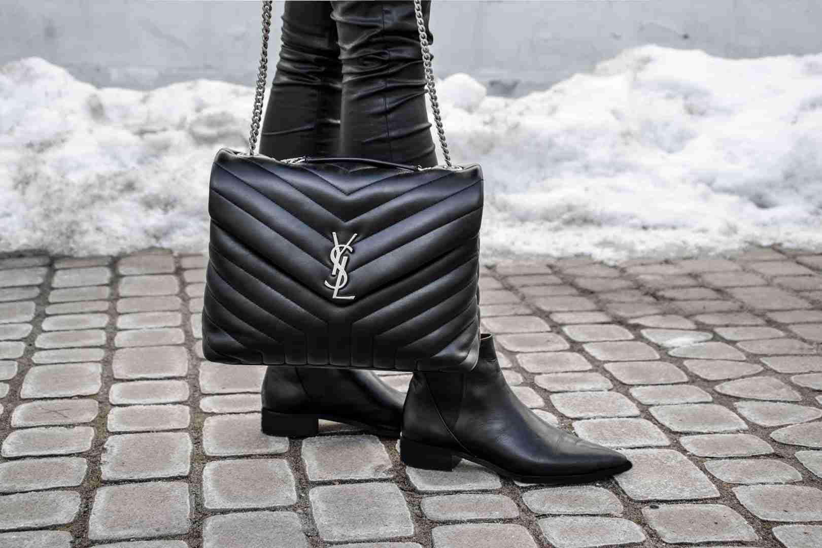 Zbliżenie na torbę YSL oraz buty.