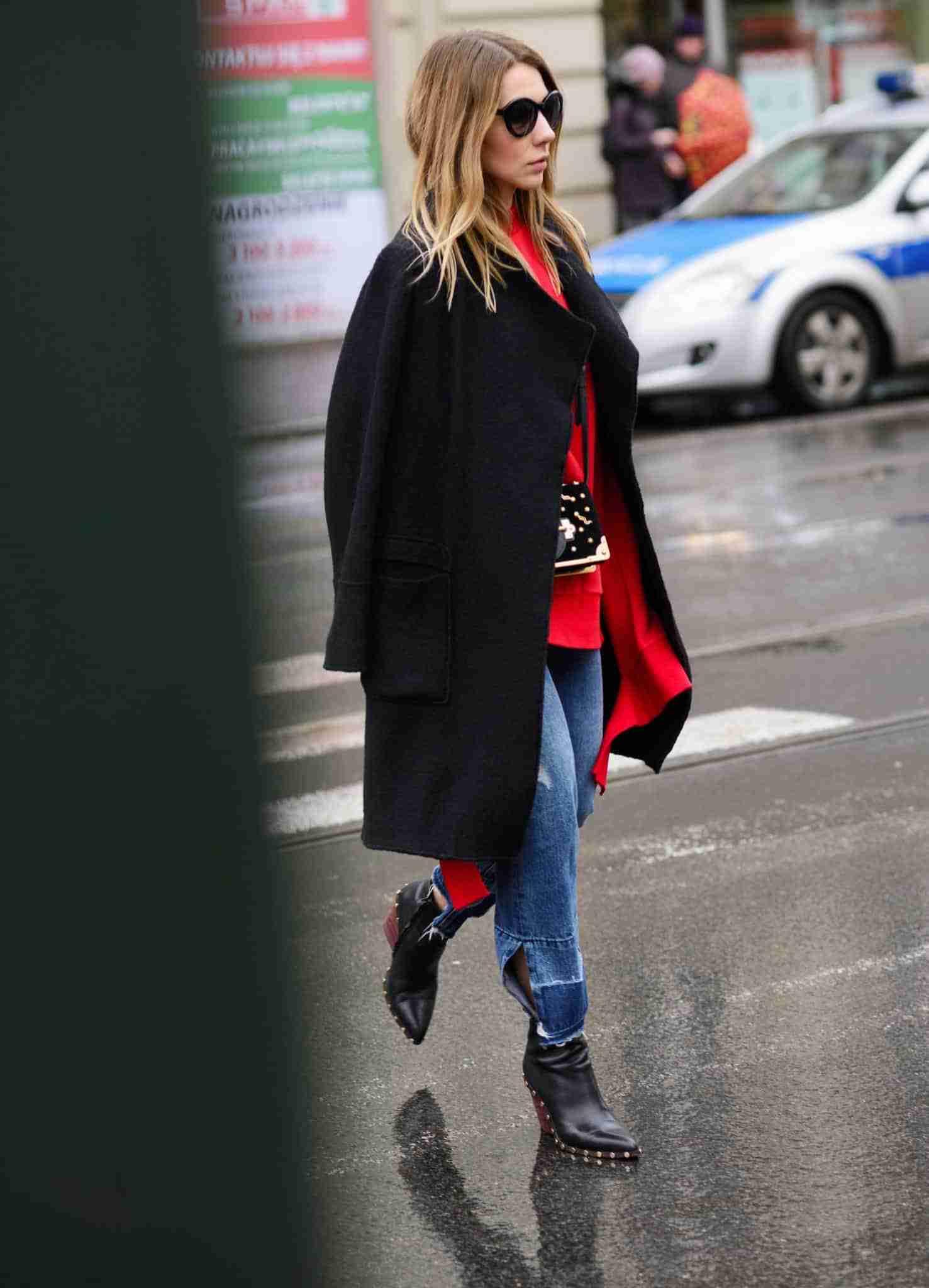 Klaudia w bluzie Vetements, czarnym płaszczu i z torebką Prada.