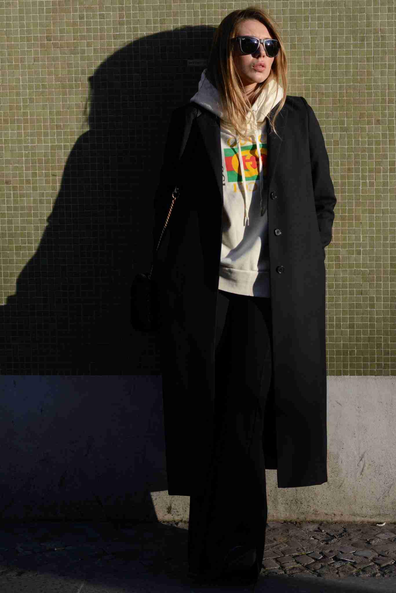 Klaudia w bluzie Gucci oparta o ścianę.