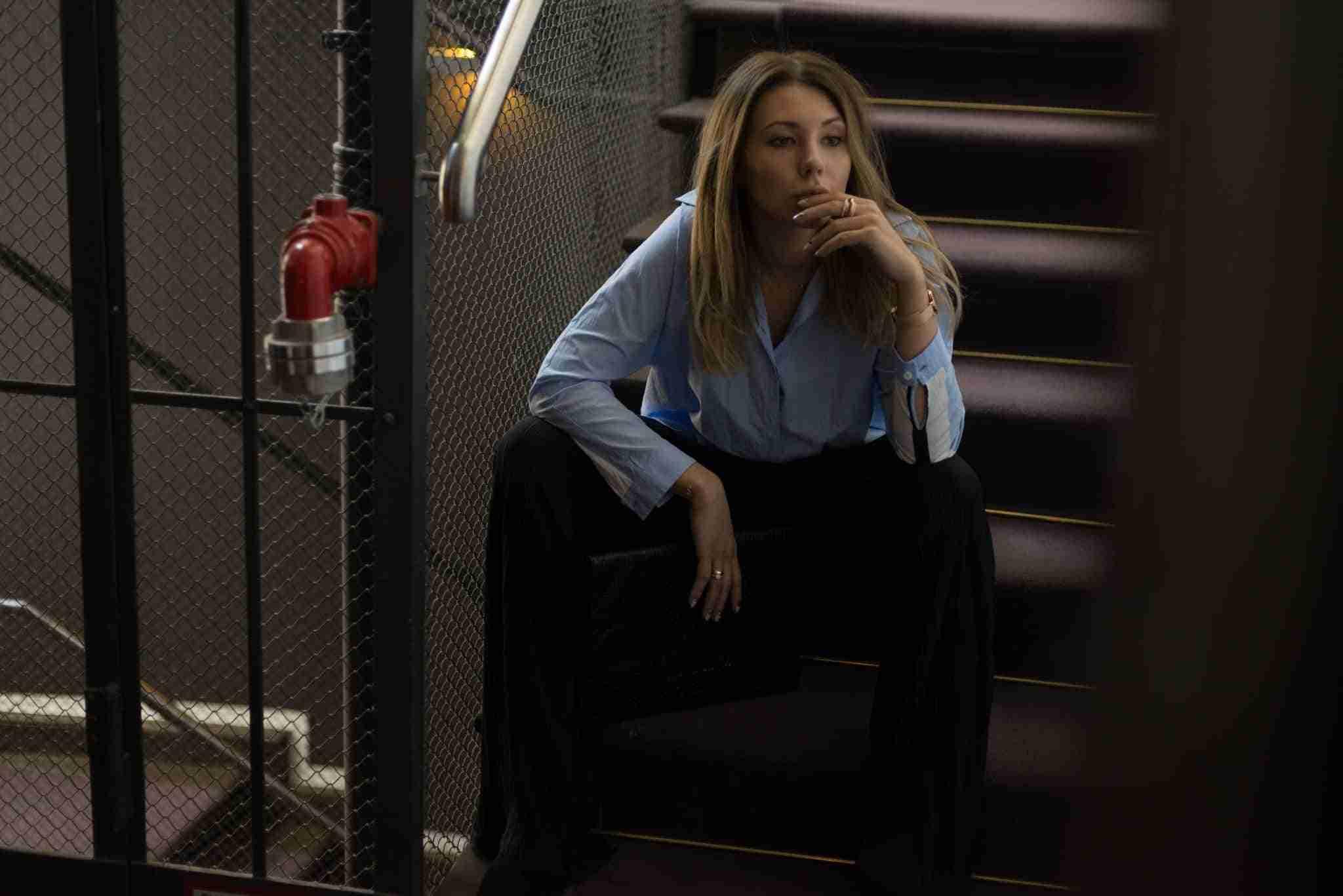 Zamyślona Klaudia na schodach.