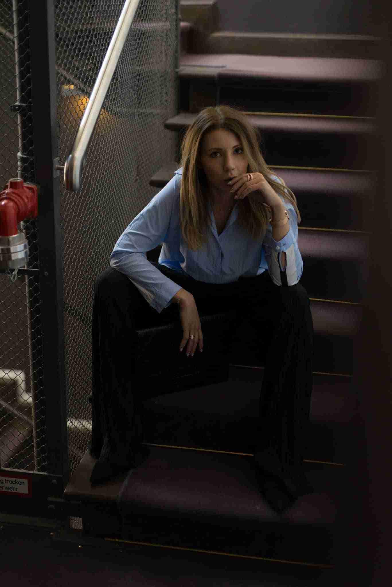 Klaudia w niebieskiej koszuli i czarnych spodniach.